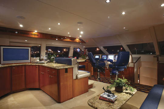 ... monitors. Abaft on the upper deck is built-in fiberglass lounge seating with storage and a solid surface table. A nicely fitted stairwell provides ...